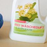 Blauer Waschball und eine Flasche Bio Wäscheduft